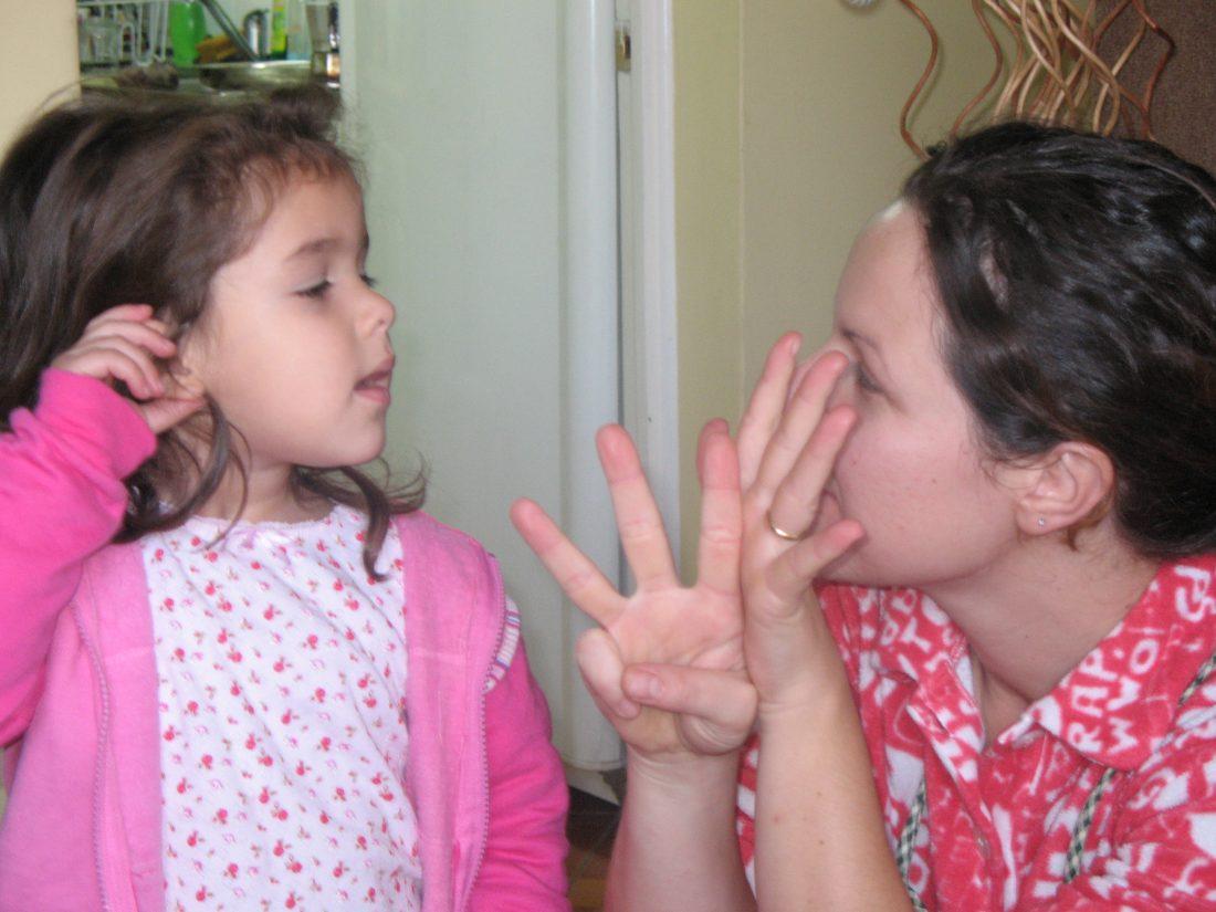 bimba coda che si comunica in lingua dei segni con la mamma
