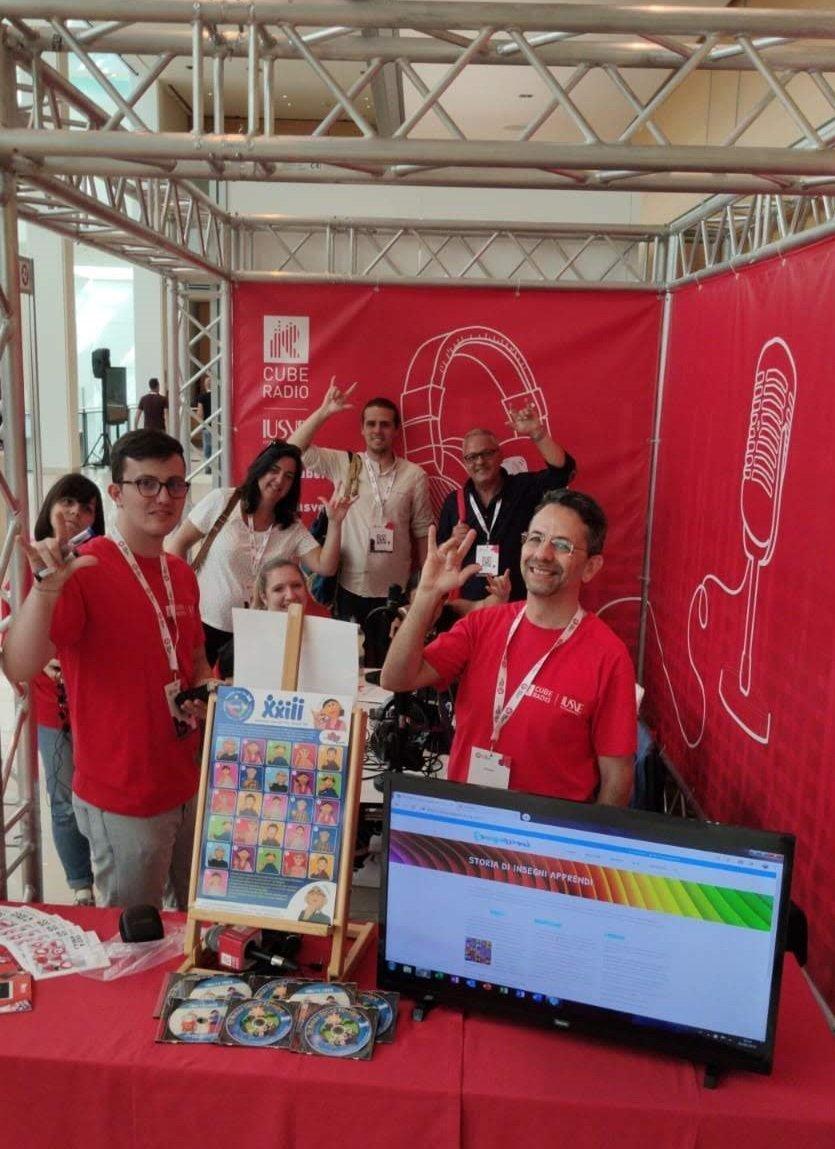 team di radio cube e insegni apprendi allo stand del web marketing festival che salutano in lingua dei segni