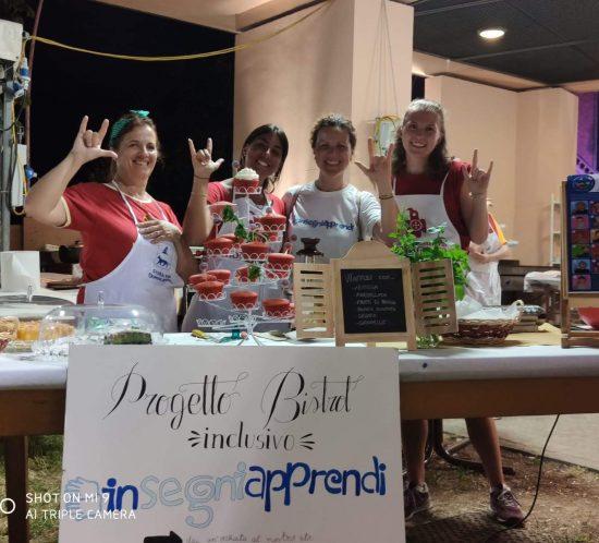 gruppo di ragazze in posa allo stand gastronomico della festa di Domagnano, promuovendo il Bistrot inclusivo in Lingua dei segni